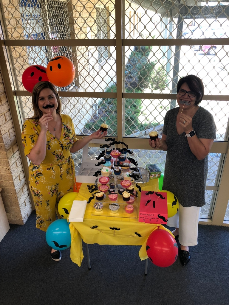 Nat and Tanja doing an excellent job showing off the delicious Movember cupcake stand we have setup today